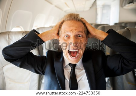 Fear of flight. Shocked mature businessman touching his head with hands and looking at camera while sitting at his seat in airplane  - stock photo
