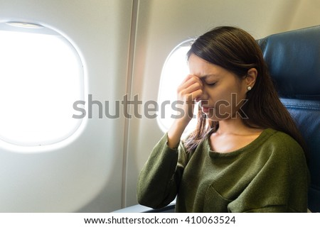 Fear of flying woman in plane airsick with stress headache - stock photo