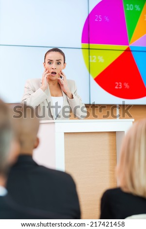Fear of public speaker. Shocked young woman in formalwear touching her face with hands while standing at the tribune in conference hall with people on foreground  - stock photo