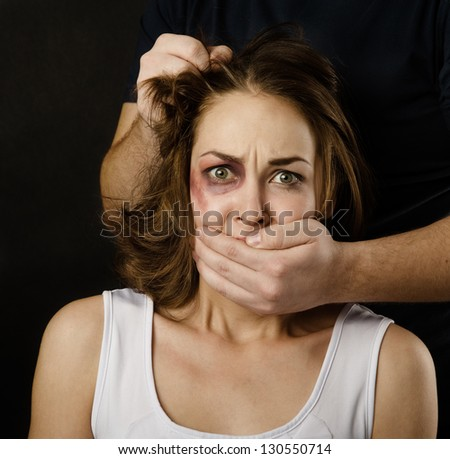 Fear of woman victim of domestic violence and abuse. on dark background - stock photo