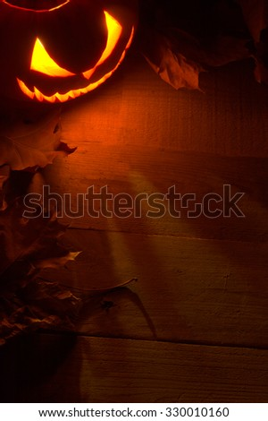 Fearful halloween red shadows background with lighting jack o lantern in the corner with red shadows on the wooden surface with autumn dried leaves