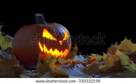 Fearful jack o lantern face among autumn leaves during night on black background - stock photo