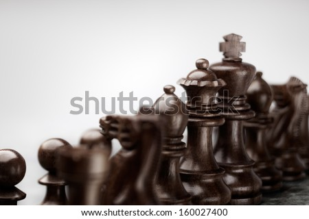 Fearless chess set standing in a row before battle ready to fight as a team. - stock photo