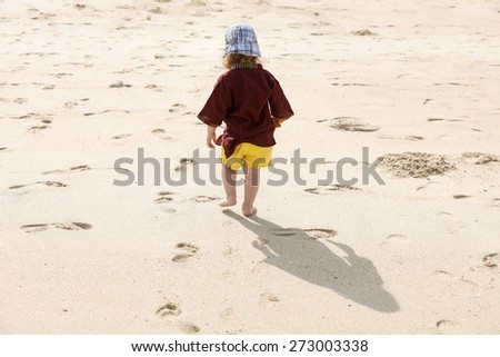 Fearless child leaving small steps in the sand, playing barefoot in the hot summer on a sandy beach.  - stock photo
