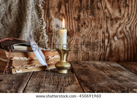 feather and book novel close to the a candle