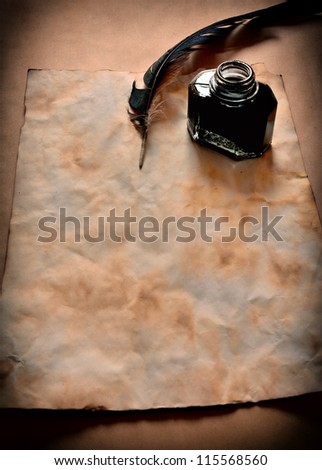 Feather and ink bottle on the old paper - stock photo