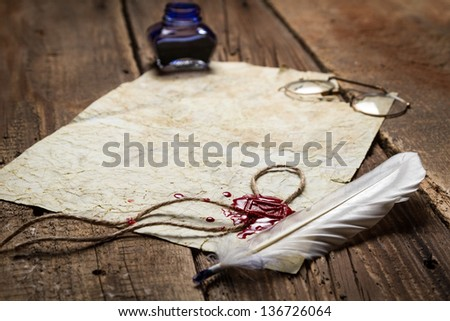 Feather and red sealing wax on old vintage paper - stock photo