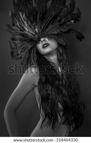 Feather helmet, beautiful brunette girl, gothic art concept - stock photo