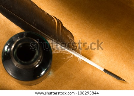 Feather ink bottle on paper - stock photo