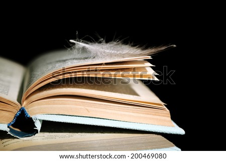 Feather lying on pages of  open book, isolated on black