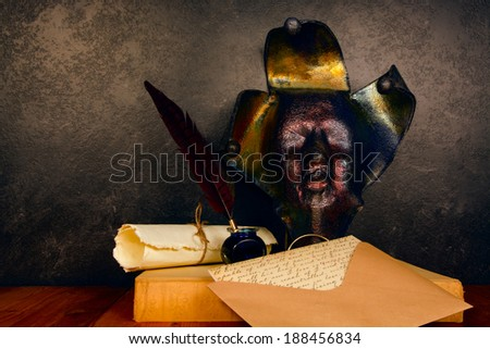 feather pen and ink with Jester mask - stock photo