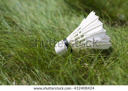 Feather shuttlecock on the lawn. Summer game on the green grass. - stock photo