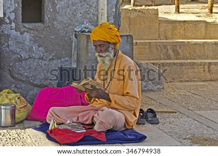 FEB 10, 2015, DWARKA, INDIA - Sadhu reads a Holy scriptures on the ghat of river Gomati