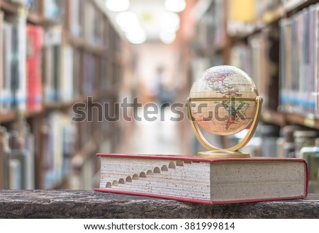 FEBRUARY 26, 2016 - BANGKOK, THAILAND: Globe model on textbook, book on old age wood table with blur abstract campus library background, stack of special knowledge resource,  educational data aisle - stock photo