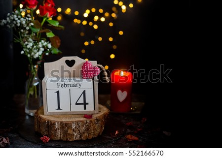 February 14 on cube calendar, red rose flower and candles, decoration for Valentines day