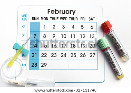 February 2016 planning calendar and blood samples in tubes / blood tubes and needle on the bottom of an appointment calendar of February 2016 - stock photo