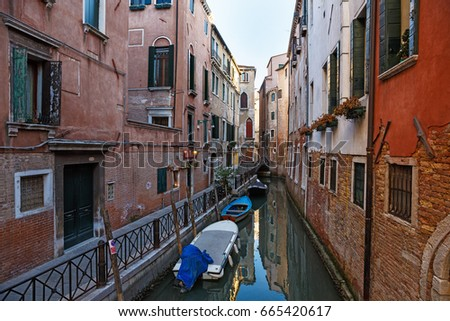 February 25, 2017. Venice street with gondolas; Boats and houses.