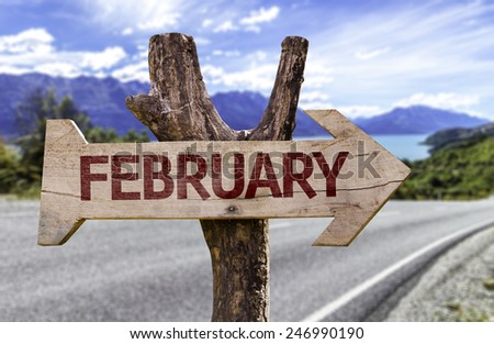 February wooden sign with a road on background - stock photo