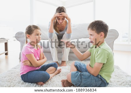 Fed up mother listening to her young children argue at home in the living room - stock photo