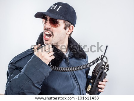 Federal agent calling it in for back up on vintage radio during an emergency going down - stock photo