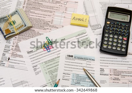 Federal Tax forms 1040 with pen, calculator and dollar