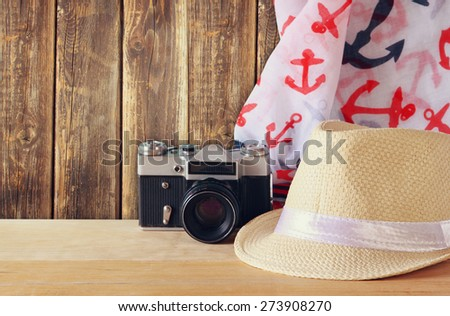 fedora hat, scarf and old vintage camera over wooden table. relaxation or vacation concept  - stock photo