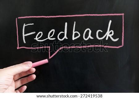 Feedback word and symbol  on blackboard using chalk - stock photo