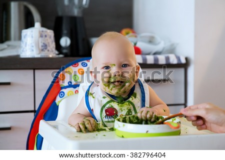 Feeding. Adorable baby child eating with a spoon in high chair. Baby's first solid food - stock photo