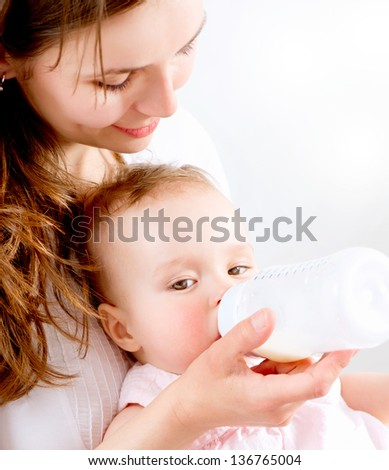 Feeding Baby. Baby eating milk from the bottle - stock photo