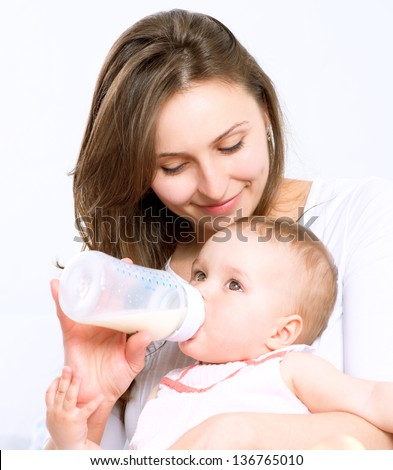 Feeding Baby. Baby eating milk from the bottle. Mother Feeds Her Newborn Baby - stock photo