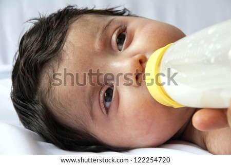 feeding baby girl with feeding bottle - stock photo