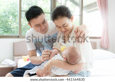 Feeding Baby infant. Asian family with mother and father feeding milk to her newborn baby infant with feeding bottle.Happy family concept.
