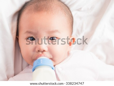 Feeding Baby. Top view of Asian Baby infant eating milk from bottle on white bed. Close-up baby looking at camera