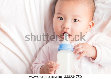 Feeding Baby. Top view of Asian Baby infant eating milk from bottle on white bed. Close-up baby looking at camera - stock photo