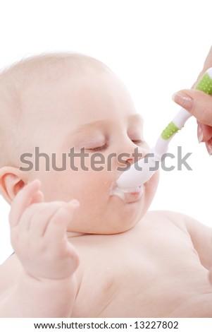 Feeding. Beautiful baby. Shot in studio. Isolated on white. - stock photo
