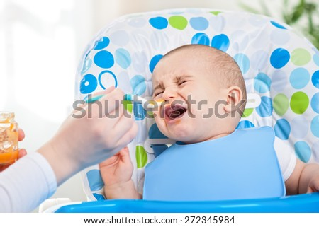 Feeding problems, little disobedient baby  - stock photo