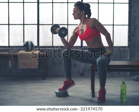 Feel that burn! A fit, sporty young woman is sitting in profile on a bench in profile, lifting weights with one hand, while resting her elbow on her knee. - stock photo