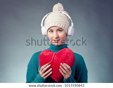 Feel the beat. Young woman with white headphones listening to the music. Music and love concept. Valentine heart beats.