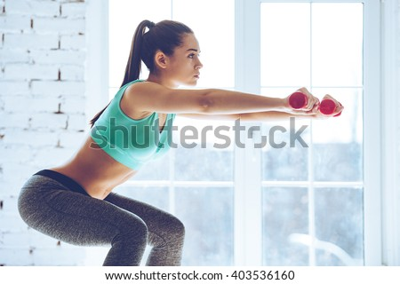 Feel the burn in buttocks. Side view of beautiful young woman in sportswear doing squat and holding dumbbells while standing in front of window at gym - stock photo