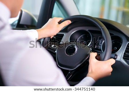 Feel the drive. Selective focus of hands of professional sale assistant sitting in the car at the wheel while testing  the car - stock photo