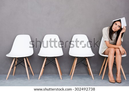 Feeling bored of waiting. Bored young businesswoman holding paper on her head and looking away while sitting on chair against grey background - stock photo