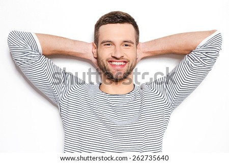 Feeling calm and satisfied. Handsome young man holding hands behind head and smiling while standing against white background  - stock photo