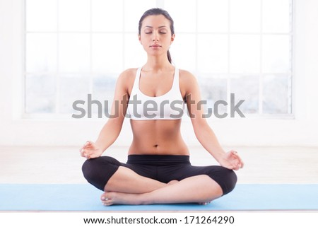 Feeling calm. Beautiful young Indian woman mediating while sitting in lotus position - stock photo