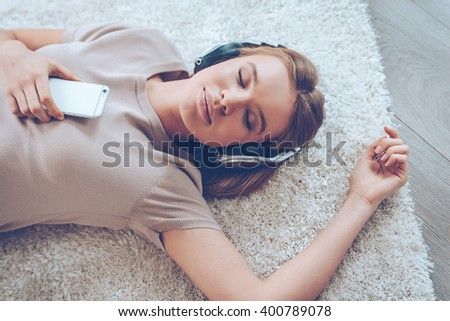 Feeling calm. Top view of beautiful young woman listening to music and keeping eyes closed while lying on carpet at home  - stock photo