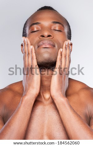 Feeling clean and fresh. Young shirtless African man touching his face with hands and keeping eyes closed while standing against grey background - stock photo