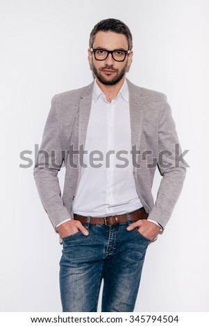 Feeling comfortable in my skin. Confident mature man holding hands in pockets and looking at camera while standing against white background - stock photo