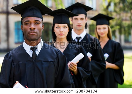 Feeling confident about their future. Four college graduates standing in a row and looking at camera - stock photo