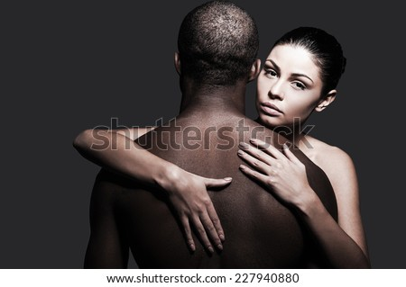 Feeling confident and protected. Beautiful Caucasian woman hugging black man and looking at camera while both standing against grey background