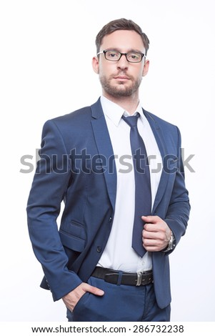 Feeling confident. Handsome bearded businessman holding his hand in the pocket with masterful look - stock photo