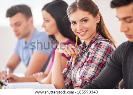 Feeling confident in her knowledge. Four cheerful students studying together while sitting at the desk while beautiful woman holding pencil and smiling at camera - stock photo